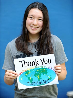 Wayland High School freshman Maya Lee holds a sign that her foundation, Team UKAPS, uses to thank healthcare workers and food banks that aid those who are fighting poverty and sickness around the world.