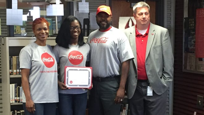 Makayla Auls (second from the left) poses with her Coca-Cola scholarship certificate after receiving $3,000 from the beverage company in May.