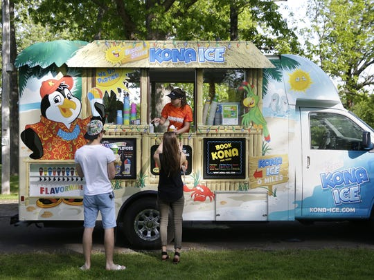 Nolan Elsbecker and his sister Olivia Elsbecker are pointed to the flavors by Nicole Heck (of Kona Ice) during a food truck rally in Appleton.