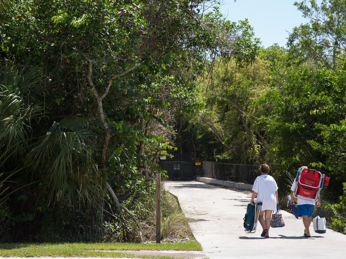 Beachgoers walk with their belongings to the Vanderbilt