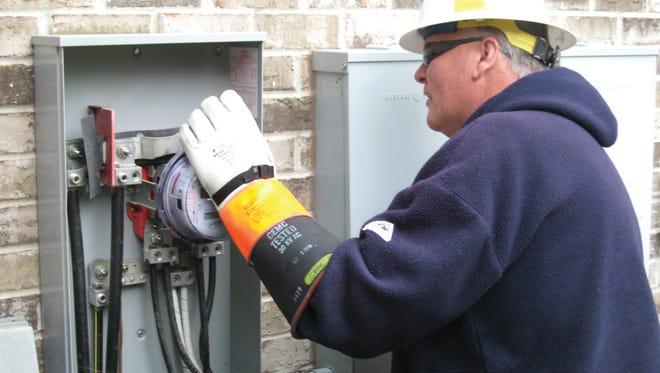 A worker installs a new advanced meter.