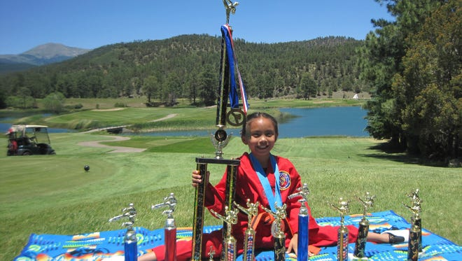 Mackenzie Kanesewah shows off her wealth of martial arts awards at the Inn of the Mountain Gods.