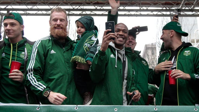 Portland Timbers, from left, Will Johnson, Nat Borchers and his son Lincoln Borchers, Darlington Nagbe, and assistant coach Pablo Moreira celebrate during the MLS champions parade through Portland, Ore., Tuesday, Dec. 8, 2015.  The Timbers defeated the Columbus Crew 2-1 Sunday in the MLS Cup soccer final. (AP Photo/Steve Dipaola)