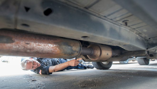 Pensacola Police Department spokesman Mike Wood points out a catalytic converter under a vehicle at the police department on Wednesday, March 21, 2018. Wood said thieves have been stealing catalytic converters and selling them for their precious metals.
