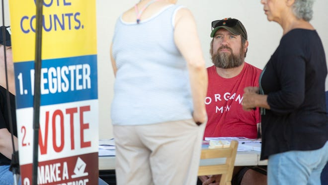 Doña Ana County Clerk Scott Krahling sits at a new voter registration booth temporarily provided for free by  the Las Cruces Farmers and Crafts Market on Saturday, July 21, 2018 after the farmers market has prohibited voter registration agents from circulating through the market.