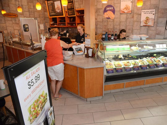 Chelsea English and Kasey McCafferty, both of Millville, serve Dolly Smith of Vineland (from right) at the Saladworks in the Cumberland Mall in Vineland.
