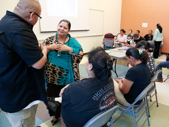 Consuelo Castillo Kickbusch visits with parents of Farmington Municipal School District students before speaking during a meeting on Thursday at the Sycamore Park Community Center.