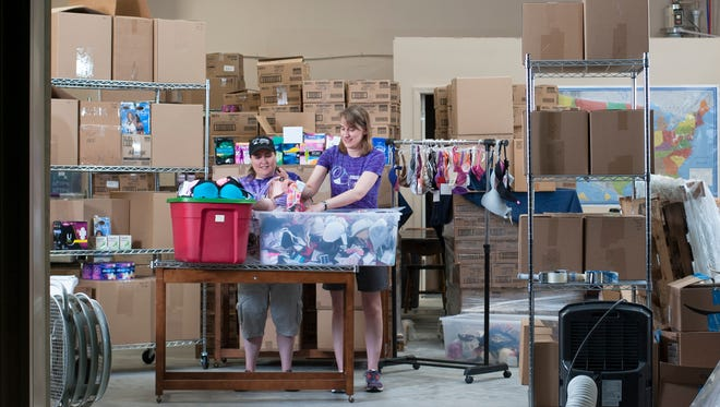 Joanie Balderstone, left, and Rebecca McIntire, founders of Distributing Dignity, make gift bags in the Cherry Hill warehouse space they use to store bra and personal toiletry donations for girls and women in need.
