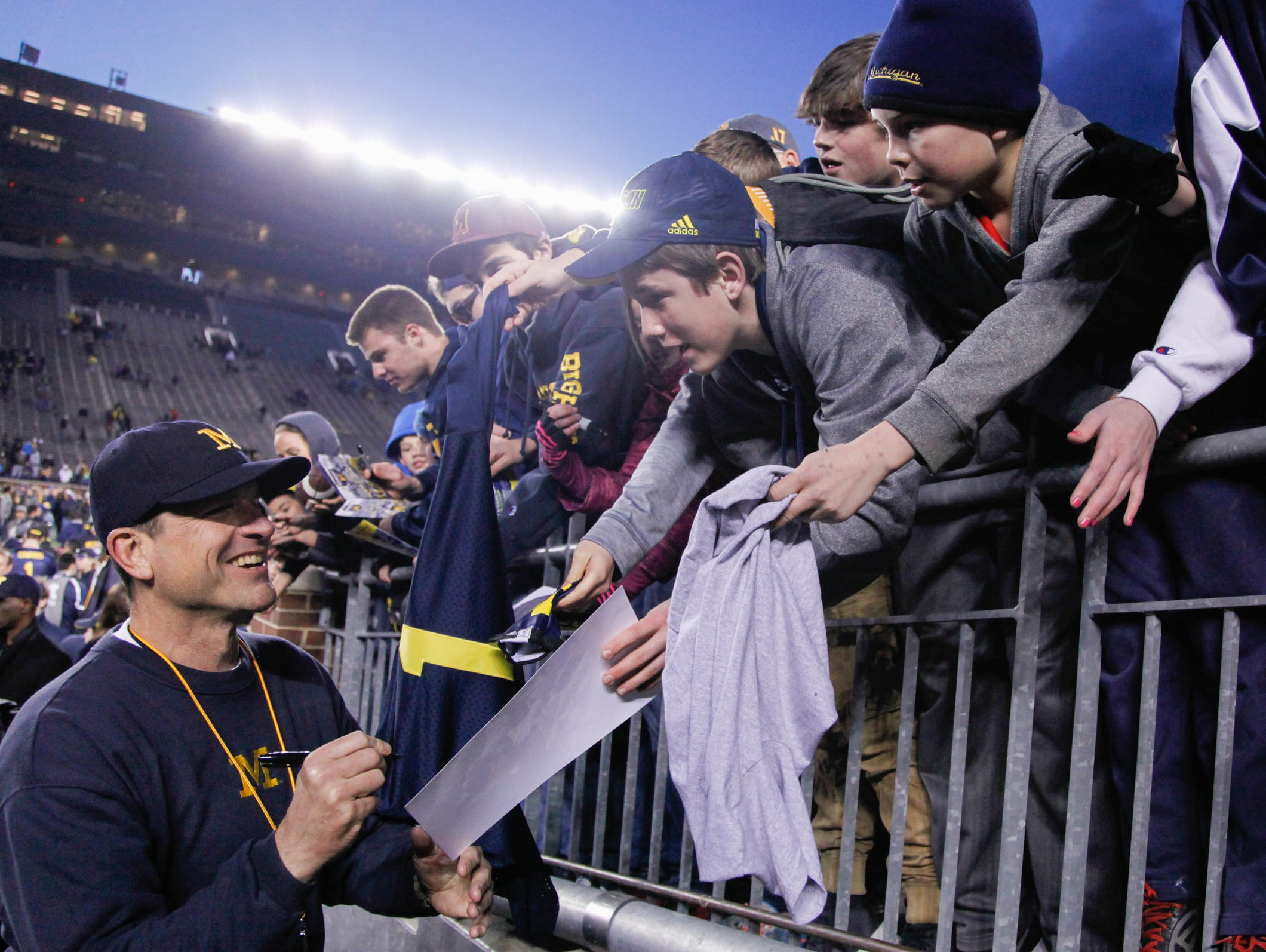 Michigan coach Jim Harbaugh signs autographs after the spring game on Friday at Michigan Stadium.