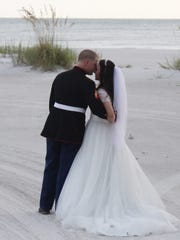 Thomas B. Walker IV, of the U.S. Marine Corps and Crystal Walker, of the U.S. Coast Guard share a moment together on Fort Myers Beach after their wedding ceremony on Friday evening.