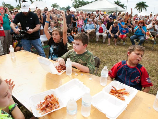Erik Jepson, 11, left, celebrates winning a bacon eating