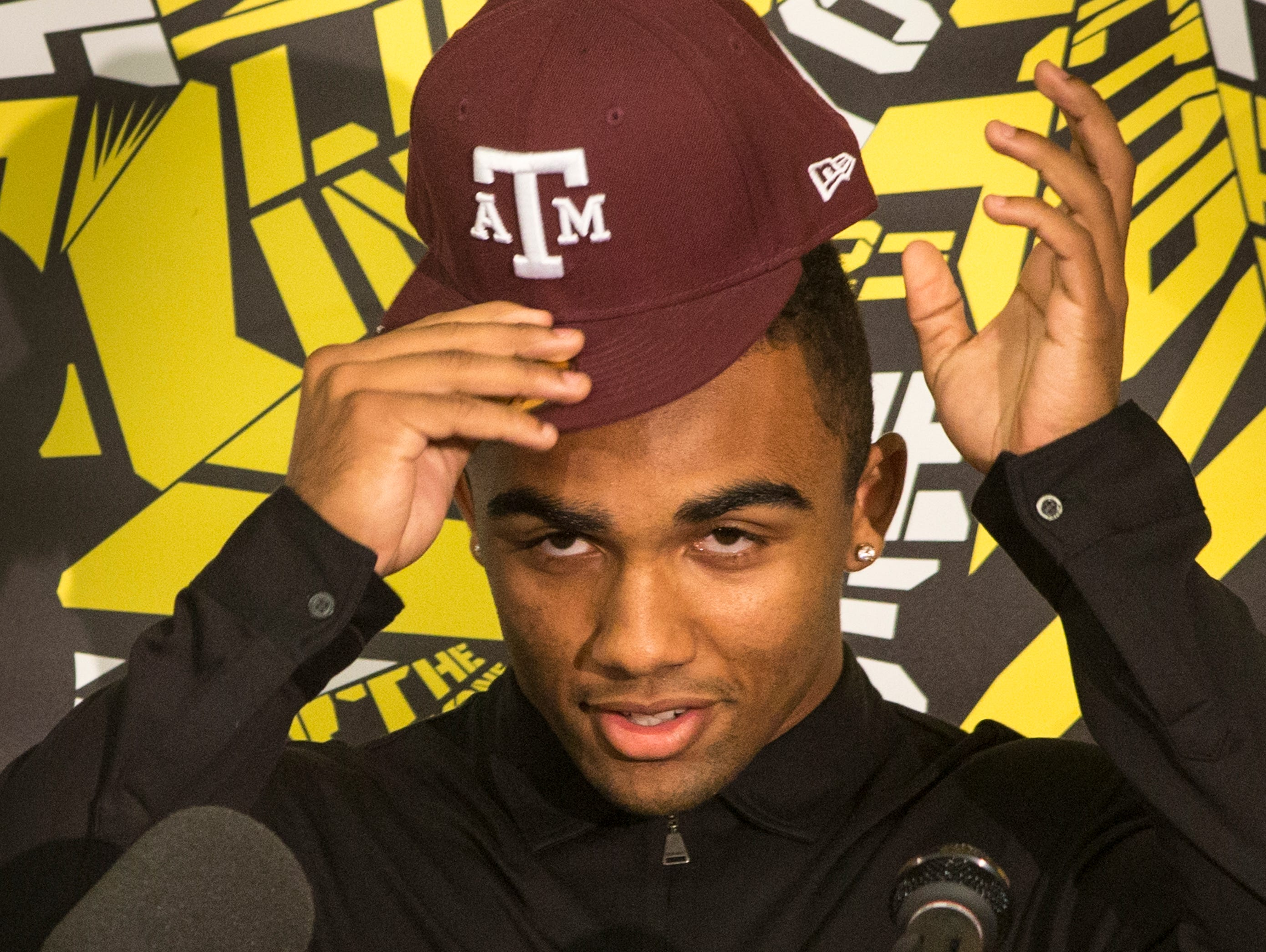 Saguaro standout football player Christian Kirk dons a Texas A&M hat as he announces his college commitment at his high school on Dec. 17, 2014.