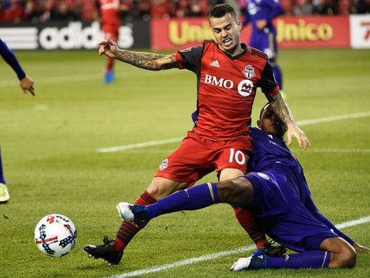 Toronto FC forward Sebastian Giovinco (10) and Orlando City SC defender Tommy Redding battle for the ball during the second half of an MLS soccer match in Toronto on Wednesday, May 3, 2017. (Nathan Denette/The Canadian Press via AP)