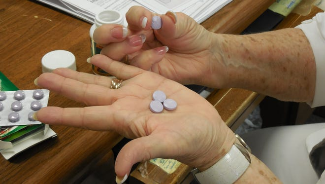 A woman holds pills from a bottle of Reumofan.