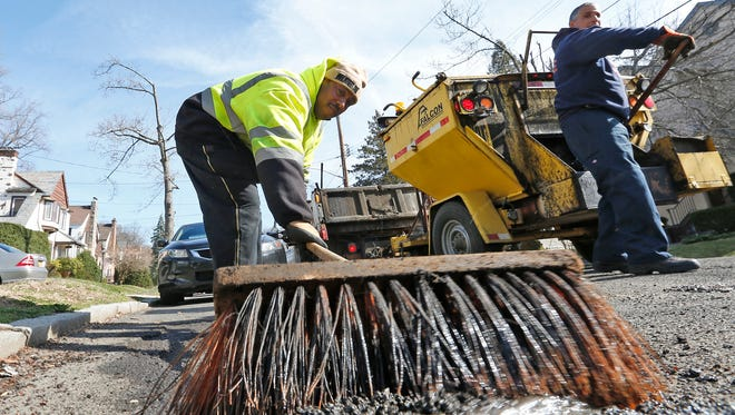 Mount Vernon Department of Public Works employee Kenny Butler sweeps debris from a pothole on Vernon Place.