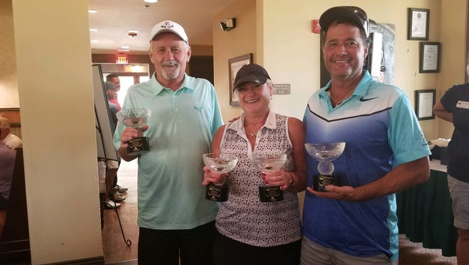 Janette Powell is flanked by teammates Daryl Graham and Russ Gonzalez as they pose with their trophies after winning the Mesquite Chamber of Commerce's13th annual Golf Tournamenton Aug. 4, 2018. Powell is holding the trophy for her husband and fellow teammate who left early due to illness.