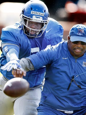 University of Memphis redshirt freshman defensive lineman Joseph Dorceus (left) strips the ball away from assistant coach Paul Randolph (right) during Tuesday morning practice. Dorceus, is the younger brother of Tigers running back Doroland Dorceus.
