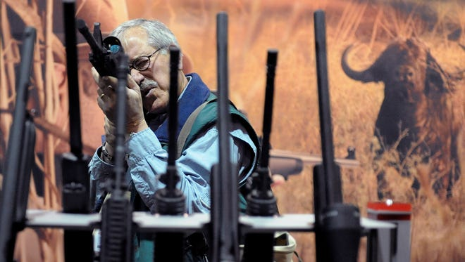 Tom Mattusch of California looks through the scope of a rifle at the 2010 Safari Club International's annual convention at the Reno-Sparks Convention Center on Jan. 20, 2010.