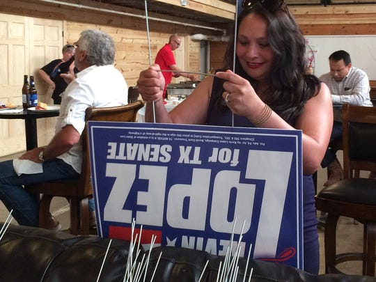 By Trish ChoateA campaign worker prepares signs promoting