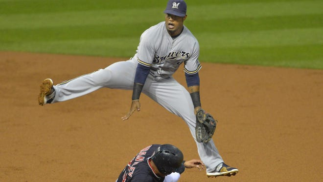 Milwaukee Brewers shortstop Jean Segura (9) turns a double play over Cleveland Indians left fielder Michael Brantley (23) in the first inning at Progressive Field on Wednesday.