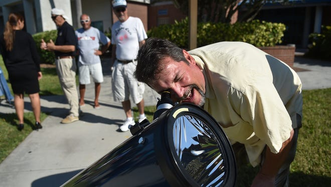 Scott Hughes, of Vero Beach, looks through one of several telescopes pointed skyward toward the sun as dozens gathered outside the Indian River State College Hallstrom Planetarium in Fort Pierce on May 9, 2016 to view the planet Mercury as it transitions across the sun. IRSC is hosting a solar eclipse watch party Aug. 21, 2017 to allow people to safely watch the event.