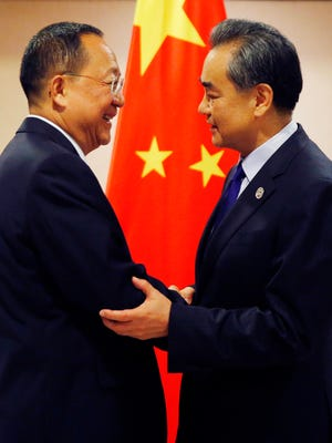 North Korean Foreign Minister Ri Yong Ho, left, is greeted by his Chinese counterpart Wang Yi prior to their bilateral meeting in the sidelines of the 50th ASEAN Foreign Ministers' Meeting and its Dialogue Partners.