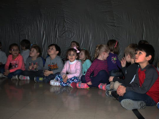 Students at Immaculate Conception School take a trip through space inside the 'Sky Dome' planetarium on Wednesday.