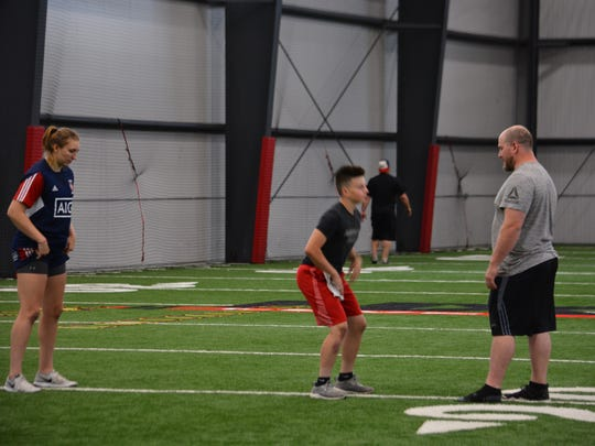 Erin Wright (left), a rugby player at Harvard, and Tyler Umland (center), a middle school student athlete in Muskego, work with Jacob Bodi, general manager and performance coach, at the NX Level Training facility on June 6. Bodi says the facility intensively tries to condition each athlete's bodies for their particular sports.