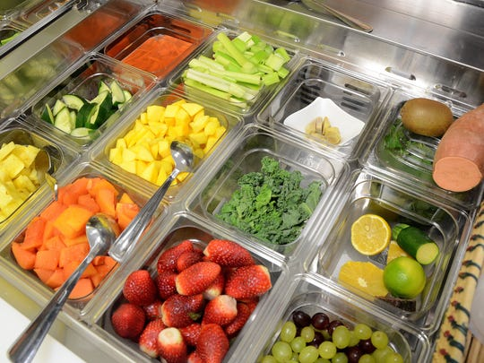 Fruits and vegetables go into smoothies at Mango Healthy Fruit & Food.
