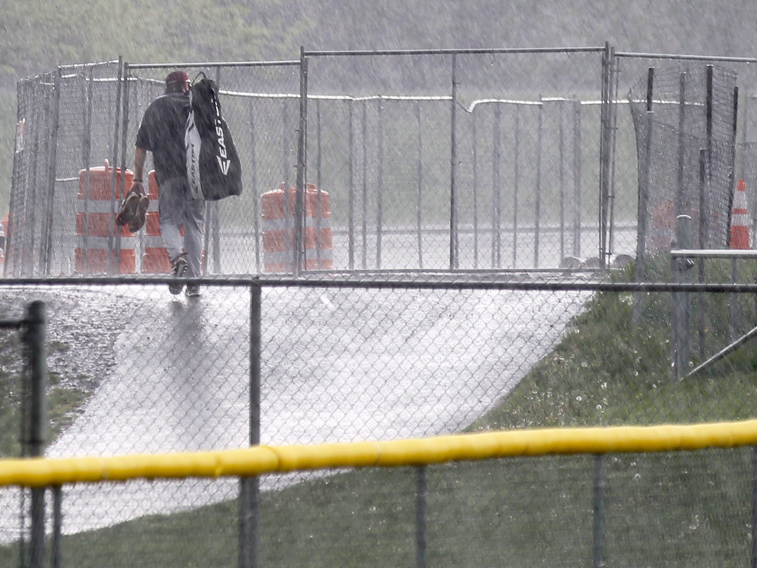 One of the coaches of Pittsford Mendon baseball heads to the parking lot in a driving rain after their game vs. Pittsford Sutherland was called off.