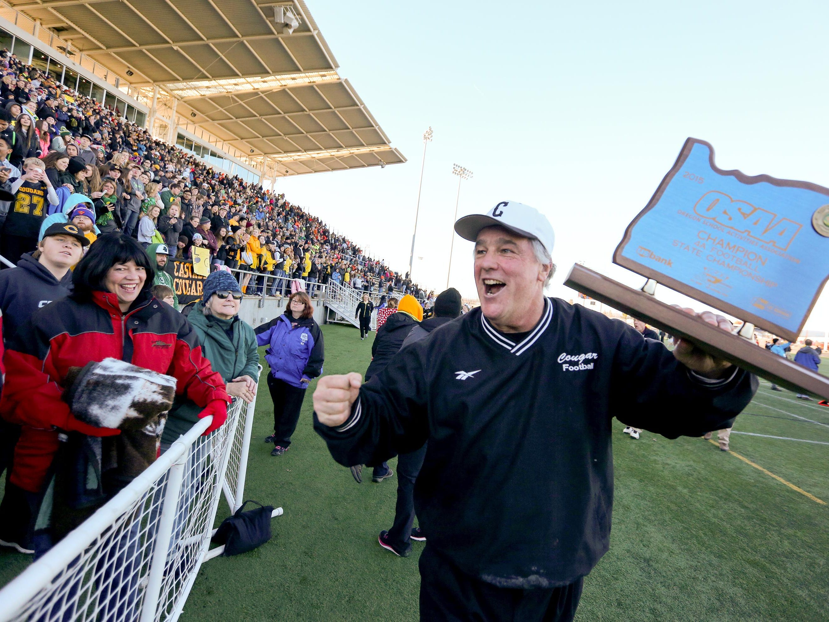 Cascade head coach Steve Turner celebrates with the championship trophy after his team won against Scappoose during the OSAA 4A state championship game, Saturday, November 28, 2015, at Hillsboro Stadium in Hillsboro, Ore. Cascade won the game 37-28.
