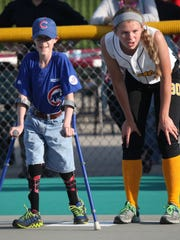 Miracle League player Nicholas Finer of Urbandale stands on first base next to volunteer Lexy Winecke during a game earlier this year at the Miracle League field in downtown Des Moines.
