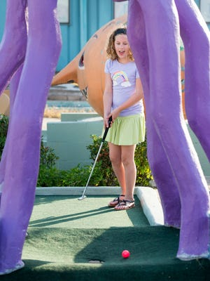 Ellie Nissim, 9, of Pensacola, reacts as she is about to sink her putt at First Tee's Goofy Golf in Pensacola on Monday, June 26, 2017.