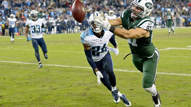 New York Jets wide receiver Eric Decker (87) is unable to hang onto a pass as he is defended by Tennessee Titans cornerback Coty Sensabaugh (24) in the second half of an NFL football game Sunday, Dec. 14, 2014, in Nashville, Tenn. (AP Photo/Mark Zaleski)