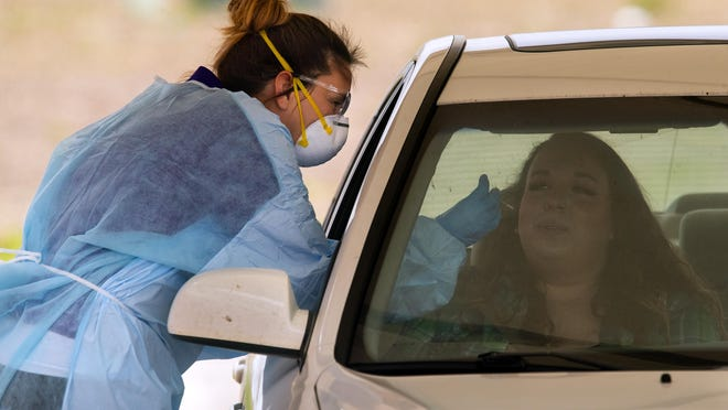 Dr. Careyana Brenham reaches in with a swab to test a patient for COVID-19 at the Sangamon County Health Clinic's drive-up testing site at 2833 South Grand Ave. East in Springfield, Ill., Tuesday, May 12, 2020.