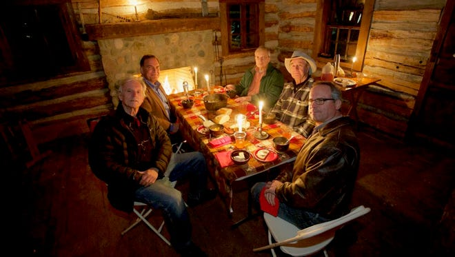 Sharing a rustic dinner at the Craig log cabin are (from left) Larry Trinkaus, Brian Kepes, John Marshall, David Baumhart and Dave Boagart.