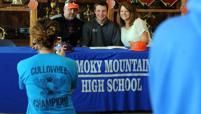 Todd and Stephanie Raleigh take a picture with their son Cal, center, after Cal signed his official letter of intent to play baseball at Clemson University on Wednesday at Smoky Mountain High School.