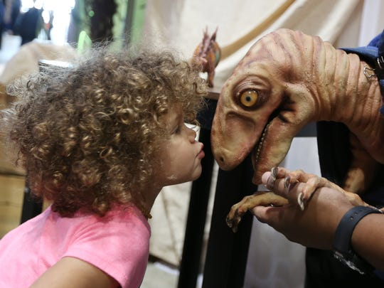 Esther Golden, 2, of Salem kisses a Velociraptor puppet at the Discover the Dinosaurs Unleashed exhibit on Sunday, Nov. 20, 2016, at the Oregon State Fairgrounds.
