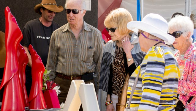 Visitors look at artwork during the Scottsdale Arts Festival in Scottsdale, Ariz., Sunday March. 10, 2013.