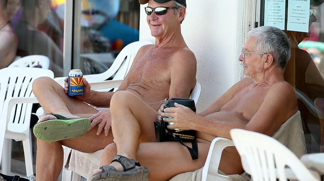 Donn Holmes (left), 63, and Ken Runo, 65, soak up some sun Friday at Shangri La Ranch, a clothing-optional community in New River. Today is National Nude Day, a holiday celebrated by nudists around the country.