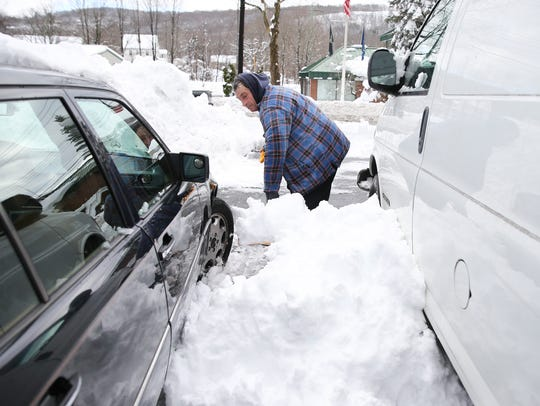 Tom Frye shovels snow from the cars at the Methodist