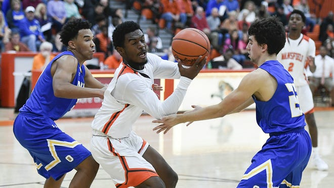 Mansfield Senior's Jornell Manns turns between Ontario's Alexander Schiffer and Jackson Todd on his way to the basket during the Tygers' season opener against Ontario on Dec. 2.