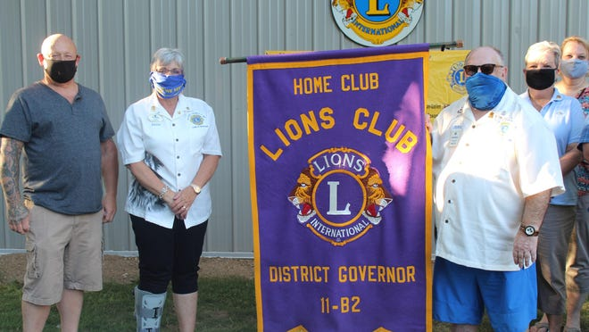 Pictured during the banner exchange are Three Rivers Lions Club president Tom McWatters, District Governor Julie Mayuiers, Immediate Past District Governor John Postelli, his wife Natalie Postelli, and Lions Club of St. Joseph president Carrie Brunsting.