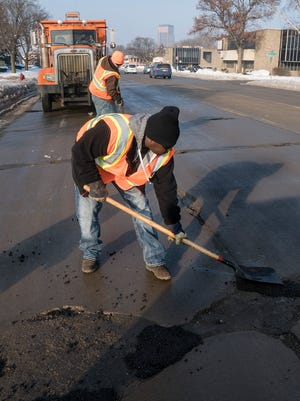 Daimon Parker and Allan Beyer patch the damaged roads. Frank Pena mans the truck that shields the workers and keeps an eye on oncoming traffic.