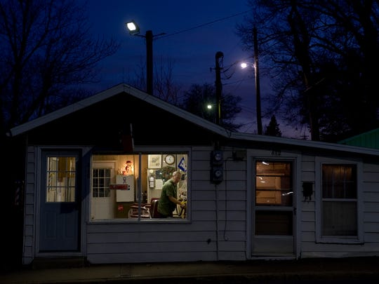 Steve Cooper closes up Cooper's Barber Shop after the sun had already disappeared for the day. The barber has been at the same location since 1967.