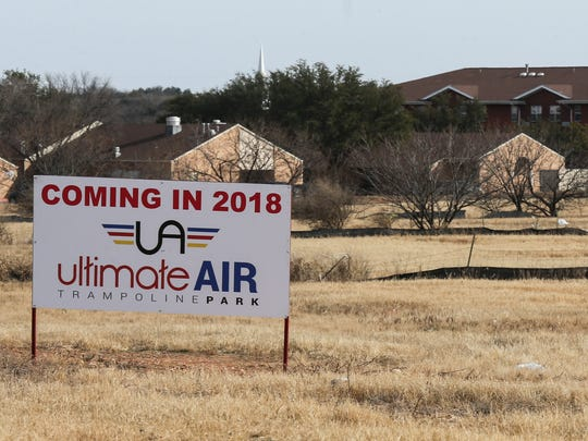 A sign for Ultimate Air Trampoline Park is posted by an empty lot behind Lowe's Home Improvement.