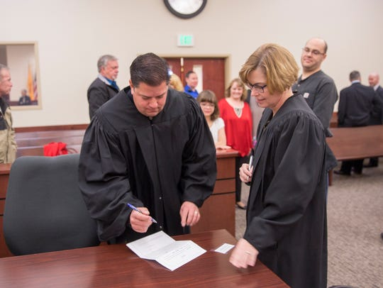 Magistrate Court Judge Erich Cole signs documents witnessed by Chief District Judge Karen Townsend on Friday after his swearing-in ceremony in Aztec District Court.