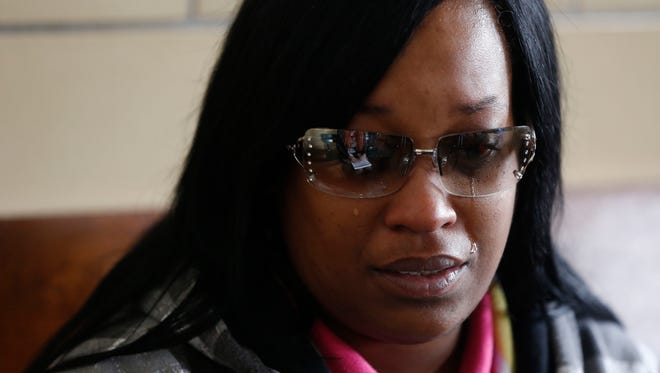 Katrina Johnson cries Thursday, March 10, 2016, at the train station in Burlington, Iowa, as she talks about the death of her son, Kedarie Johnson, before getting on a train bound for Chicago with his ashes.