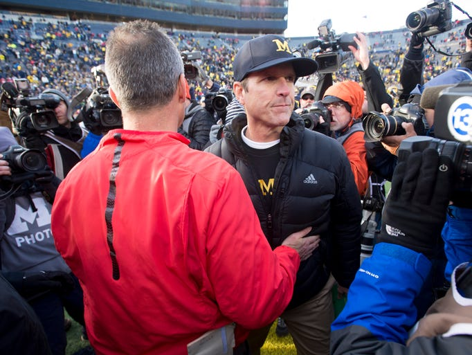 Michigan head coach Jim Harbaugh shakes hands with