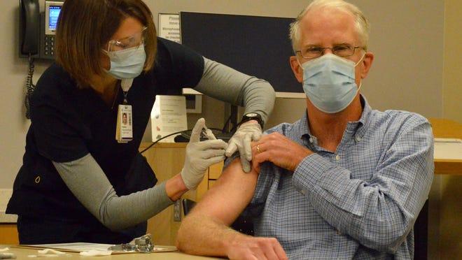 A Holland Hospital nurse administers the COVID-19 vaccine to a hospital staff member Friday, Dec. 18.
